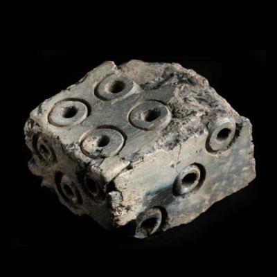 Un dé de l'Âge Viking, endommagé par le feu et présentant une numérotation incohérente, découvert lors des fouilles de Coppergate, York (Royaume-Uni). Photo par Jorvik Viking Centre